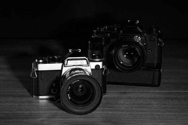 Close-up of cameras on table against black background