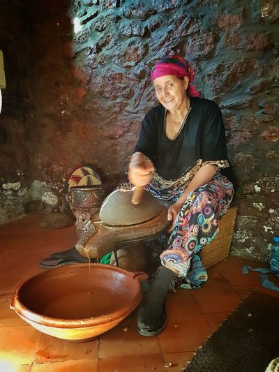 Only Women Portrait Looking At Camera Real People Women Day One Woman Only Indoors  Sitting Preparing Argan Oil Argan Oil Morocco Maroc Grinding Argan Working Working Woman Argan Oil Maroc Grinding Wheel Grinding Stone Grinding Argan