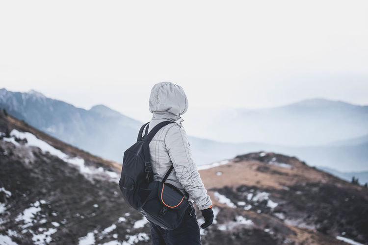 Man with backpack standing on mountain against clear sky