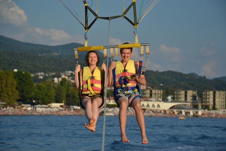 Full length portrait of smiling couple parasailing over river