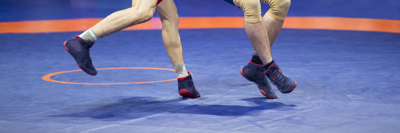 Low Section Of Athletes Wrestling On Mat