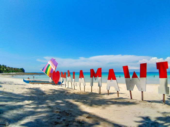 Multi colored umbrellas on beach against clear blue sky