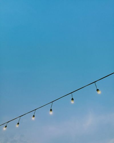 Low Angle View Of Illuminated Lighting Equipment Hanging Against Clear Blue Sky