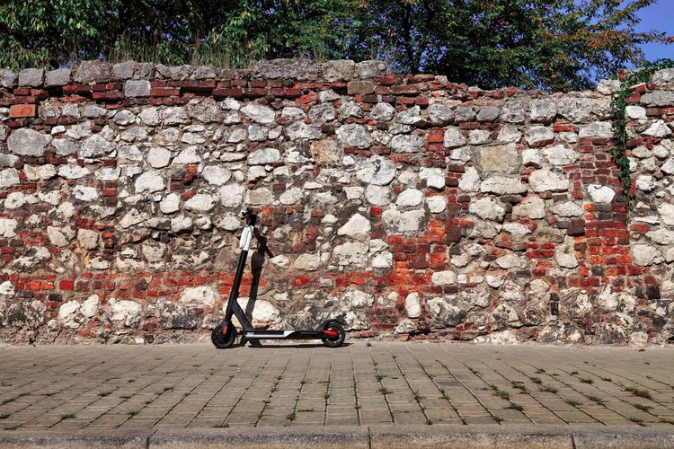 Bicycle on footpath against wall