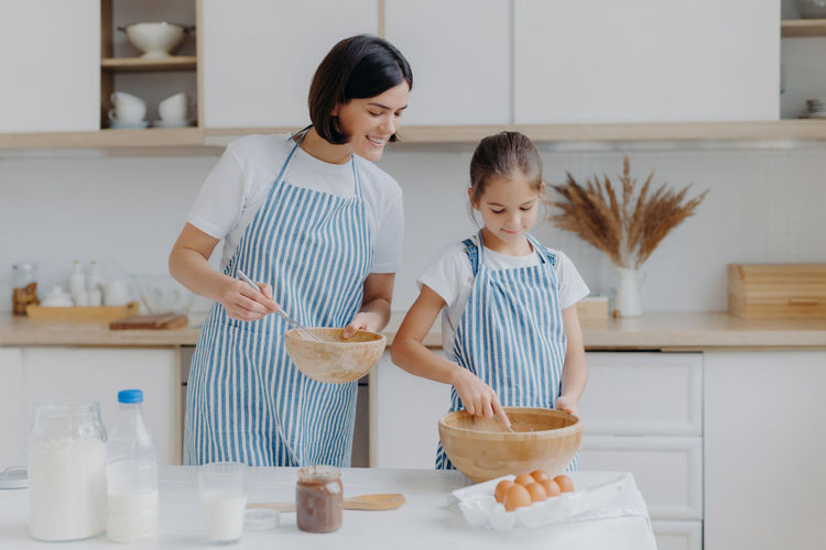 Mother and daughter standing in kitchen at home