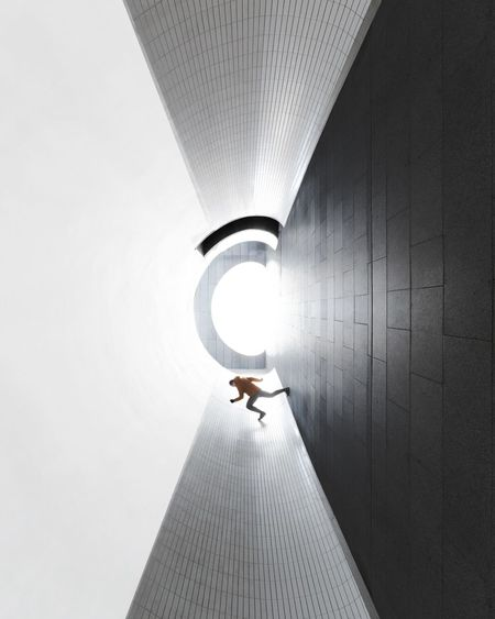 Rear view of person walking on illuminated ceiling