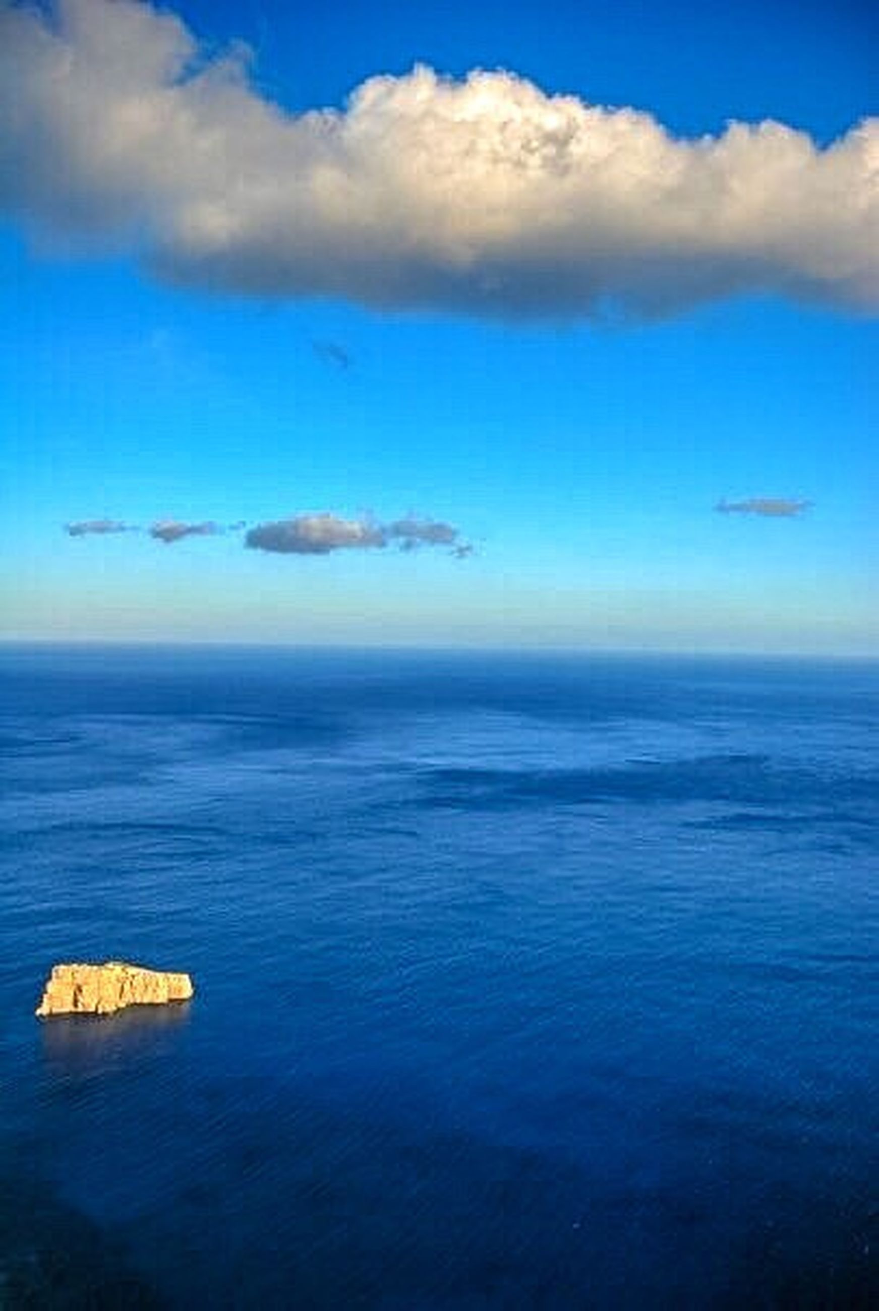 sea, water, horizon over water, blue, scenics, tranquil scene, tranquility, beauty in nature, seascape, sky, majestic, idyllic, waterfront, calm, nature, ocean, cloud, cloud - sky, non-urban scene, coastline, outdoors, day, atmosphere, aerial view, vibrant color, rock formation, solitude, no people, remote, vacations