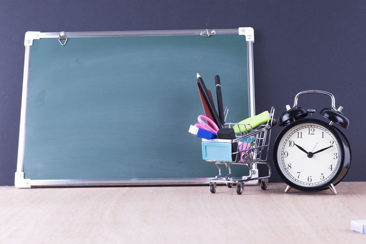 Shopping cart with school supplies by blackboard and alarm clock against wall