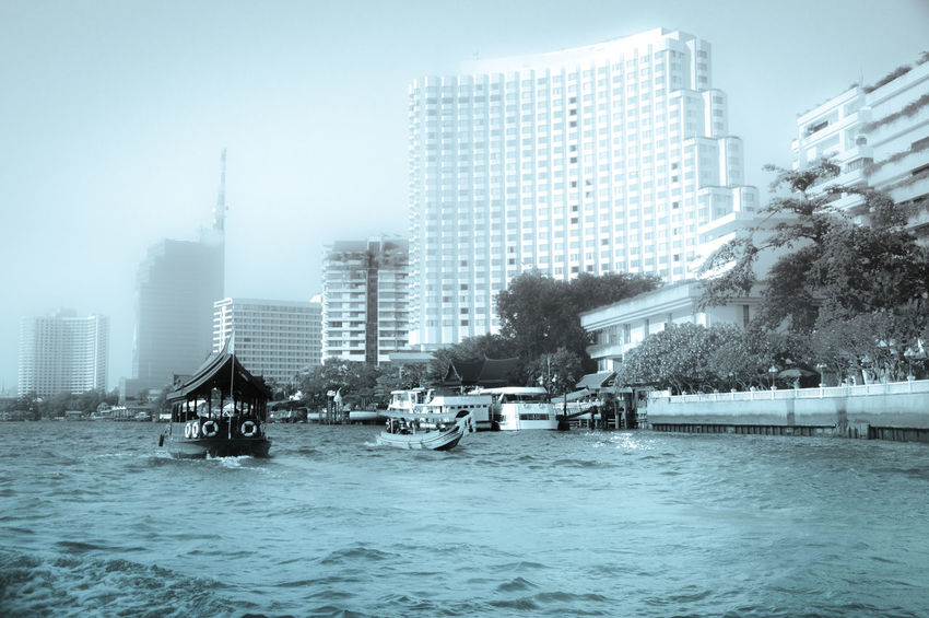Skyscraper Architecture City Urban Skyline Building Exterior Water Modern Built Structure Sky Cityscape Outdoors Downtown District Office Day No People Tree Chao Phaya River Bangkok Thailand Foggy Morning Fog In The City Travel Photography Monochrome Photography Traditional Thai Boats