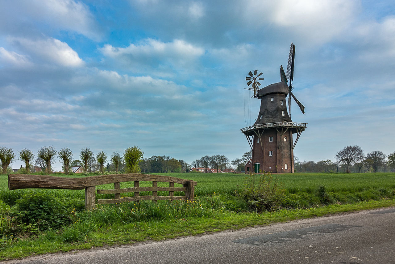 TRADITIONAL WINDMILL IN FIELD AGAINST SKY