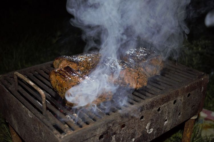 Close-Up Of Meat Steaks On Barbeque At Night