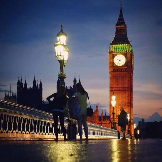 People standing on promenade by big ben at dusk