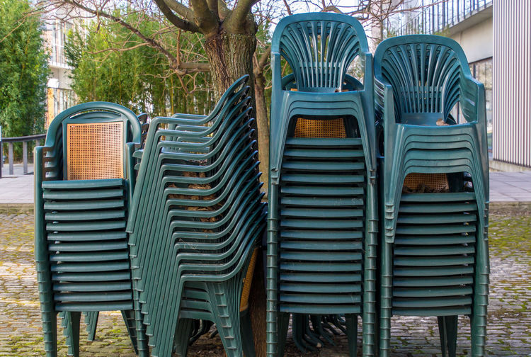 Stack Waiting For Summer Chairs Day Green Chairs Large Group Of Chairs Large Group Of Objects No People Outdoors Pile Pile Of Chairs Plastic Chairs Stack Of Chairs Tree