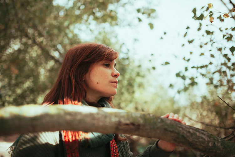 Low angle view of young woman looking away in forest