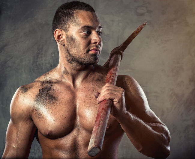 Shirtless muscular worker holding pick axe against wall