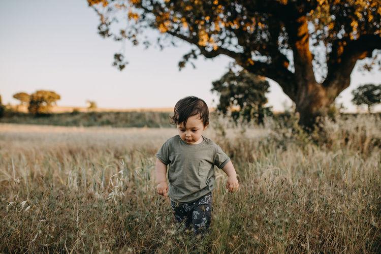 Boy standing on field against sky