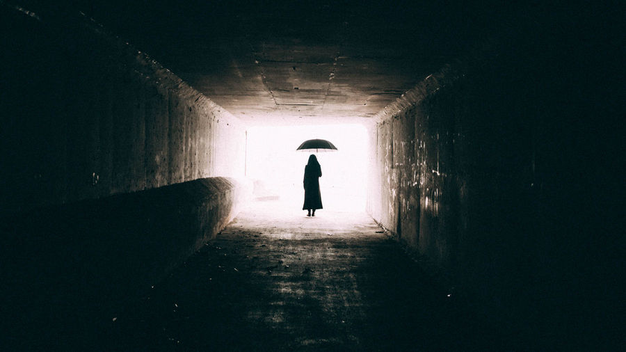 Rear view of silhouette woman walking in tunnel