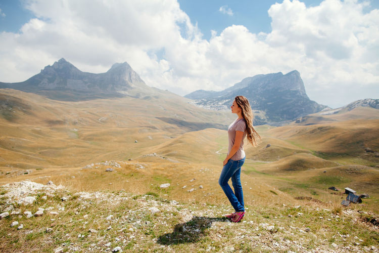 Side view full length of young woman standing on mountain