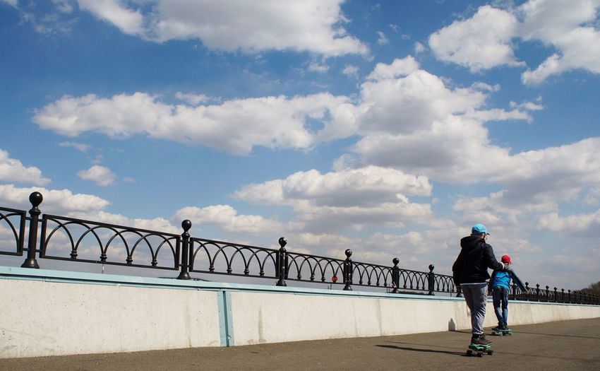 Rear view of boys skateboarding on bridge against sky