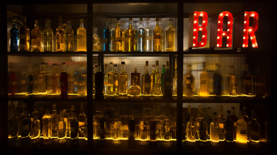 Illuminated drink bottles on shelve at bar