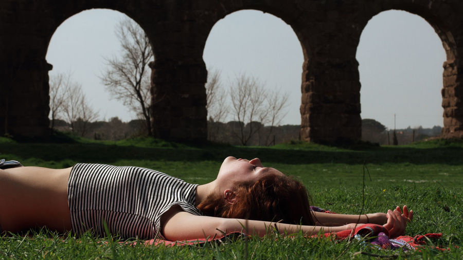 Aqueduct Arch Architecture Casual Clothing Color Curiosity Day Field Full Length Grass Lawn Lying Down Meditation Outdoors Park Person Relaxation Resting Roman Side View Tranquility Young Adult