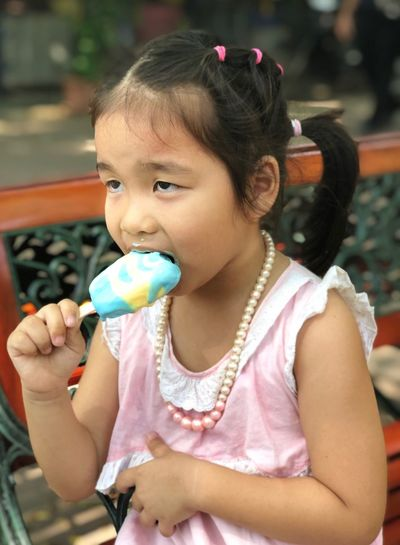 Girl eating ice cream in city