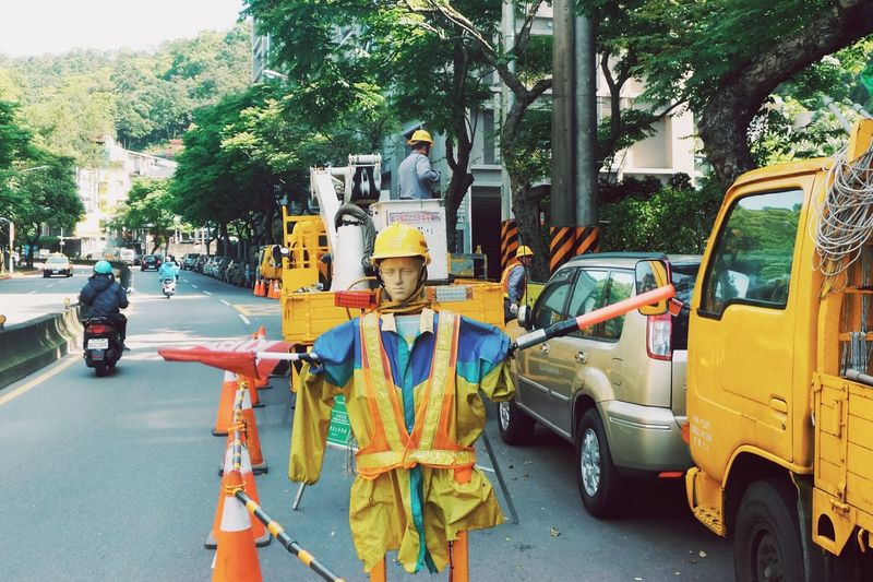 Mannequin With Helmet On Road By Traffic Cones