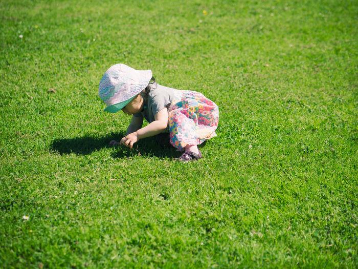 Side view of girl kneeling on grassy field