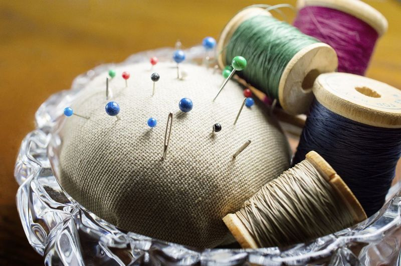 Close-up of pin cushions and spools in containers on table
