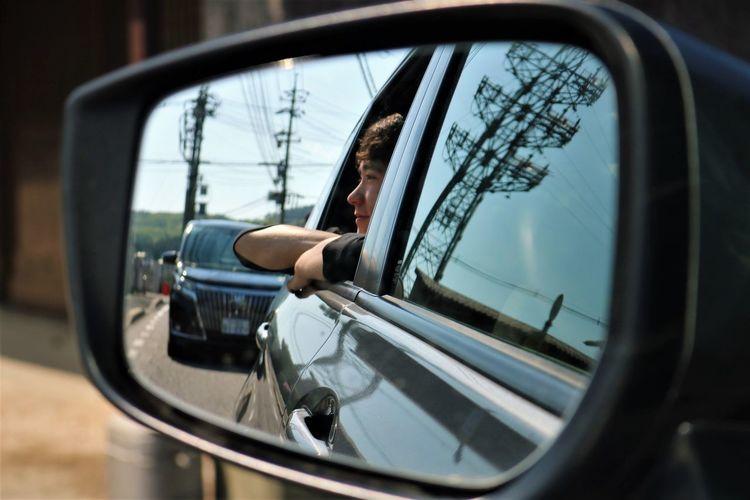 Reflection Of Teenage Boy Seen In Side-View Mirror