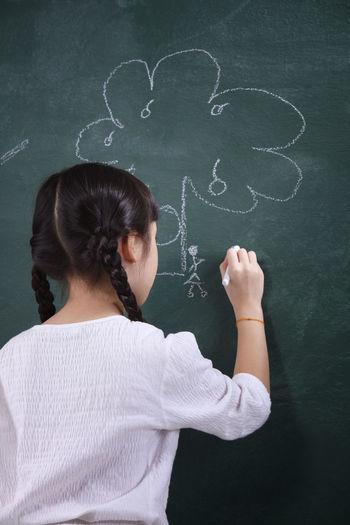 Rear View Of Girl Drawing On Blackboard