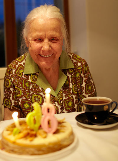 Age Anniversary Birthday Cake Candle Candlelight Creativity Female Food And Drink Good Mood Grandmother Granny Happy Home Indoors  Jubilee Old One Person Senior Smile Table Tradition Woman