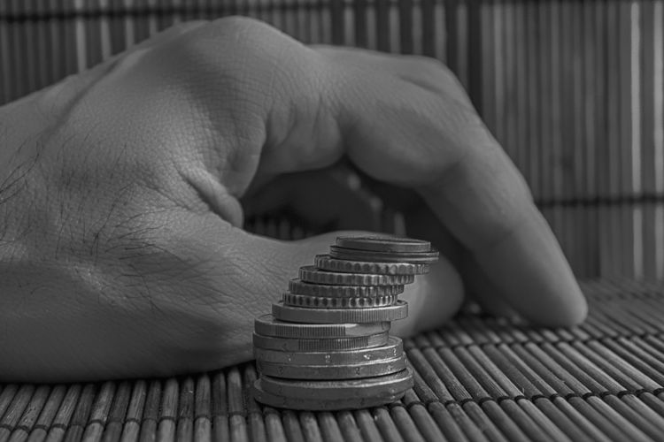 Cropped hand by stacked coins on table
