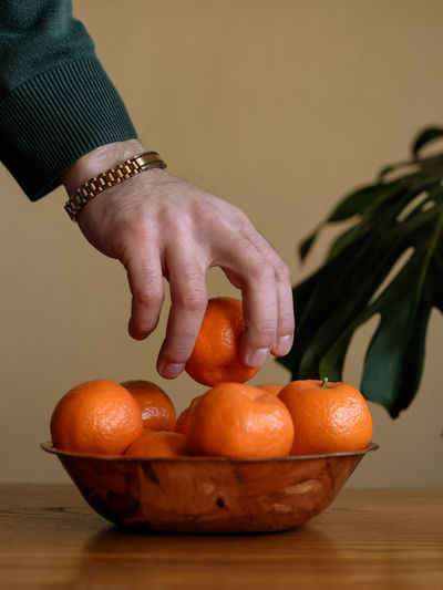 Close-up of hand holding orange on table