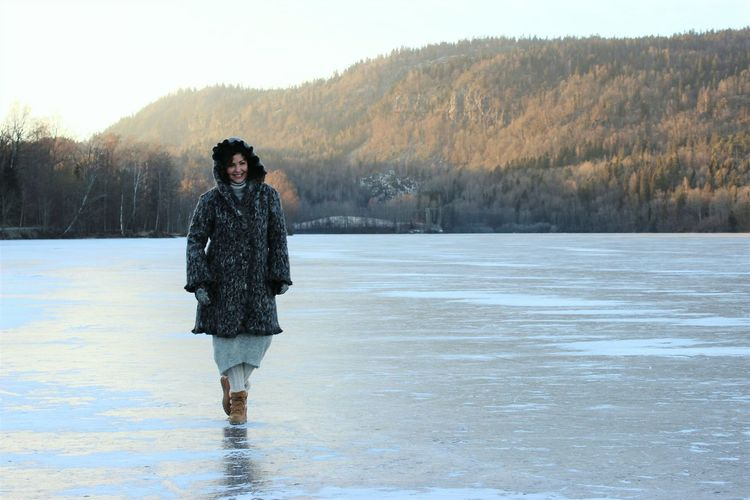 Smiling mid adult woman walking on frozen lake against forest