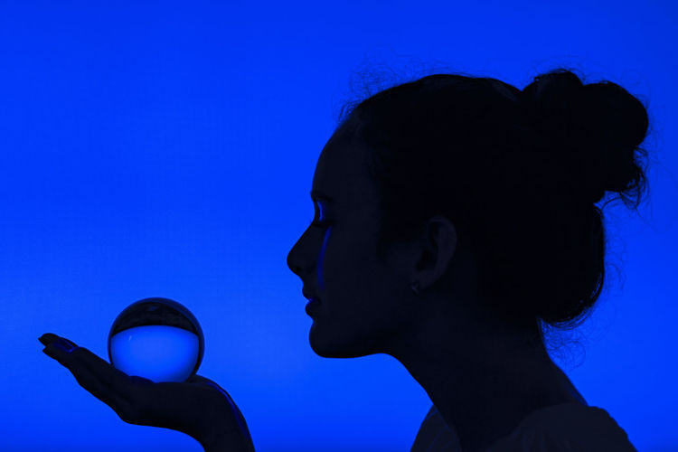 Close-up portrait of young woman against blue background