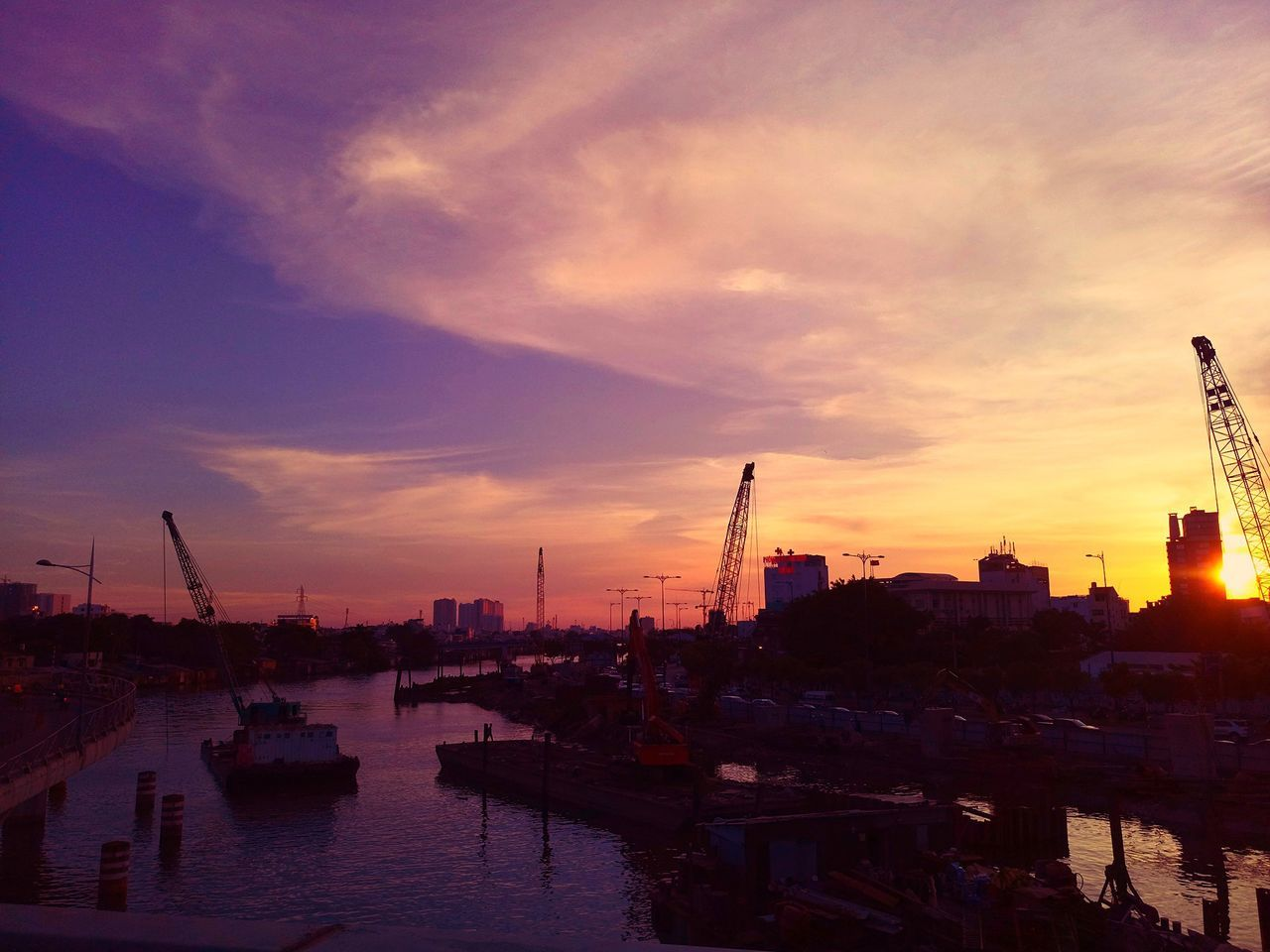 sunset, sky, cloud - sky, orange color, nautical vessel, built structure, architecture, building exterior, no people, transportation, silhouette, crane - construction machinery, city, water, crane, mode of transport, industry, travel destinations, outdoors, commercial dock, harbor, cityscape, smoke stack, nature, factory, shipyard, day