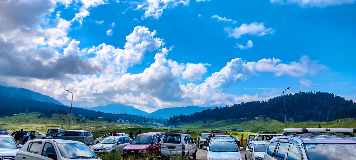 Panoramic view of cars and mountains against blue sky