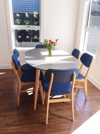 Flower vase in table amidst chairs at home