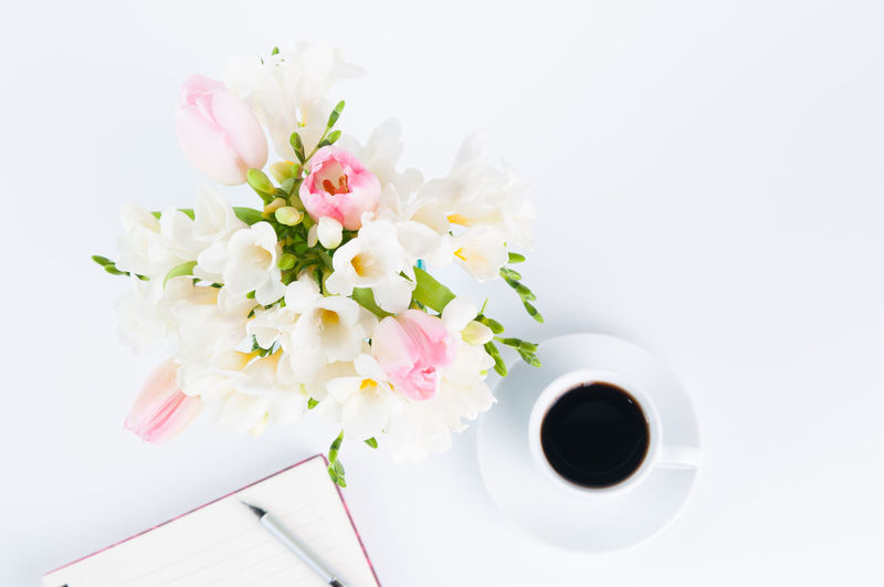 Directly above shot of black coffee with diary and flowers over white background