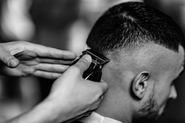 Cropped image of barber cutting man hair in shop