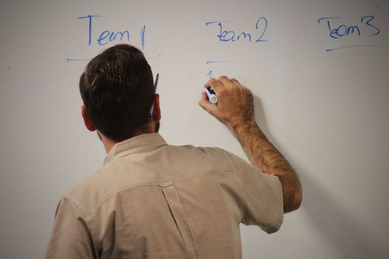 Rear view of businessman writing on whiteboard in office