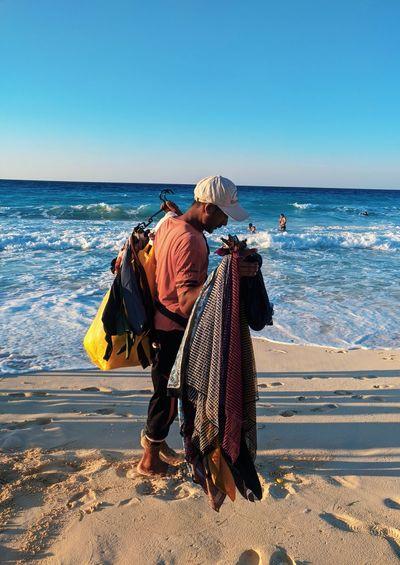 Man holding handmades at beach against clear sky
