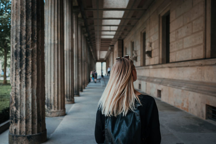 Rear view of woman standing in corridor of building