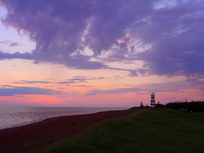Lighthouse On Hill By Sea Against Cloudy Sky During Sunset