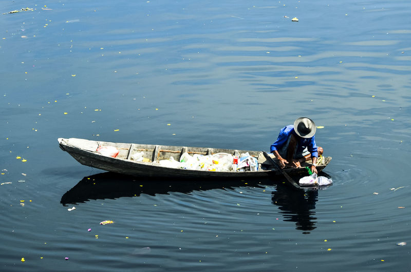 High angle view of man in boat collecting plastic