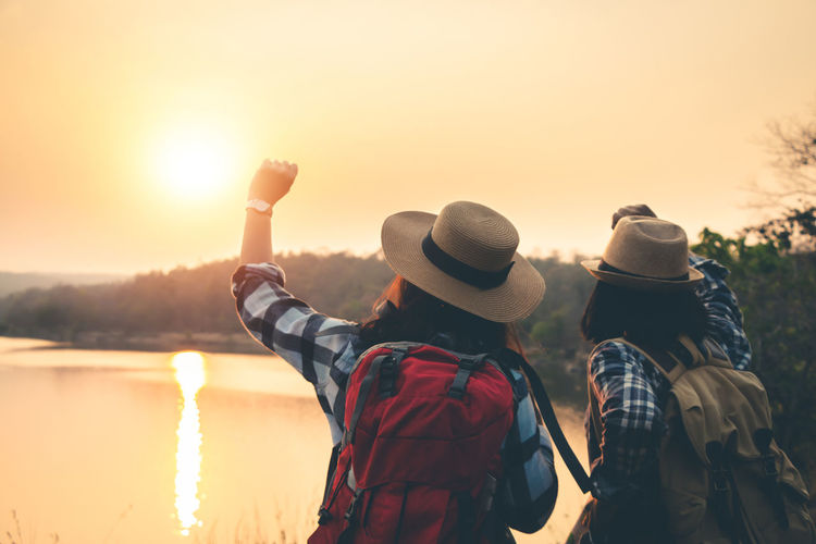 Two People Nature Sunset Sky Beauty In Nature Outdoors Landscape Travel Backpack Backpacker Women Sunlight Leisure Activity Real People Rear View Lifestyles Hat Water Bonding People Adult