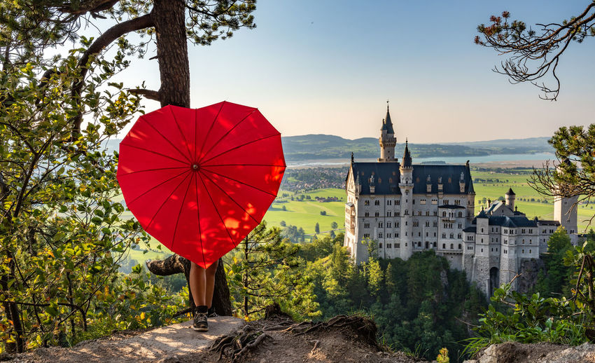 Low section of person holding red heart shape umbrella against historic building