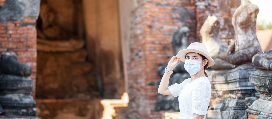 Portrait of woman wearing mask standing against ancient temple