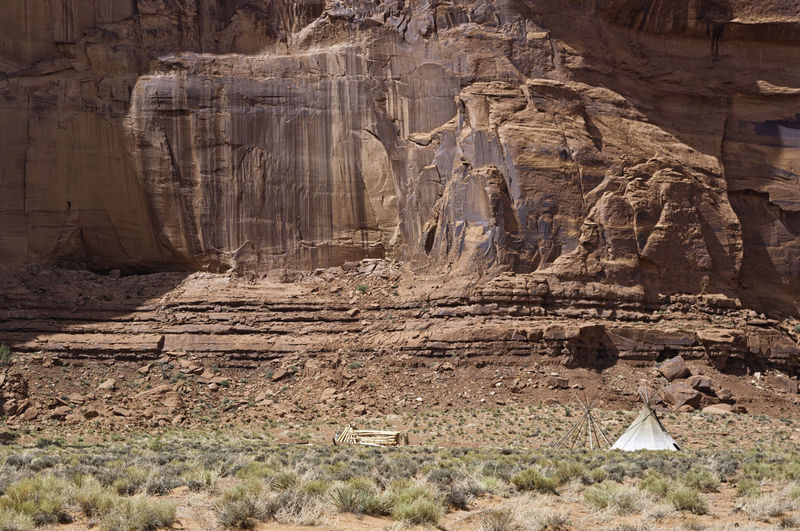 Native Indians tent in front of a red rock cliff in a remote spot in the famous Monument Valley, USA. Navajo traditional camp in the desert. Concept for adventure and solitude American Arizona Desert Indian Native USA Utah America Ancient Arid Cherokee Cliff Historic Lonliness Monument Mountain Navajo No People Old Primitive Rocks Solitude Tent Traditional Valley